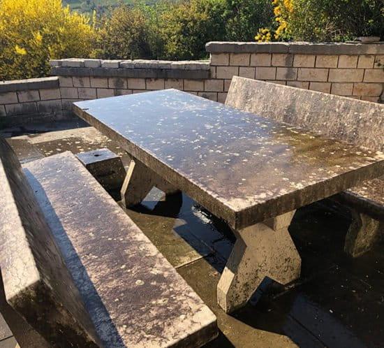Tavolo e pavimento in pietra da pulire da muschi e licheni